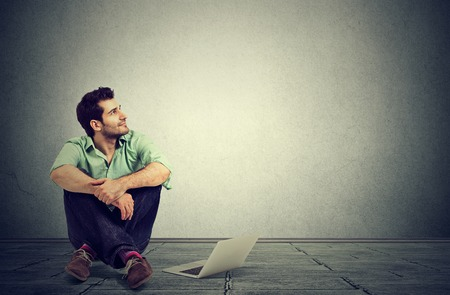 Young man with laptop computer sitting on a floor planning next step daydreaming