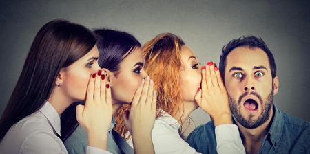 Tres mujeres jóvenes susurrando entre sí y al sorprendido hombre asombrado en la oreja. Concepto de comunicación boca a boca. Emoción humana cara expresión reacción