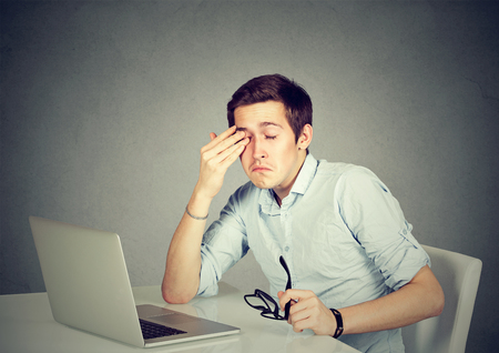 eyestrain: Young businessman rubbing his tired eyes after long working hours in office