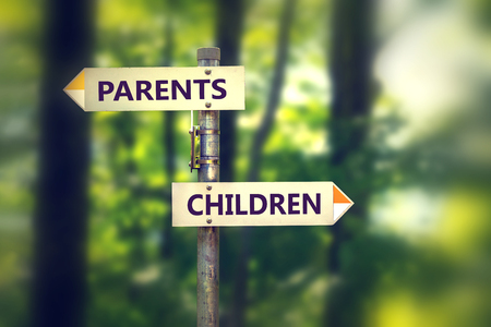Signpost in a park with arrows pointing in two opposite directions Children and Parents.
