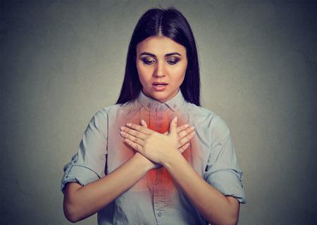 喘息の発作や呼吸の問題は灰色の背景に持つ若い女性