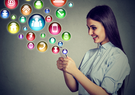 Mobile communication technology concept. Happy young woman using texting on smartphone with application symbols icons flying out of screen