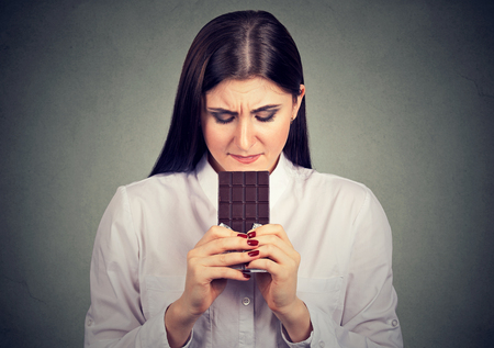 craving: Portrait sad woman tired of diet restrictions craving sweets chocolate bar isolated on gray wall background. Human emotions. Nutrition concept.