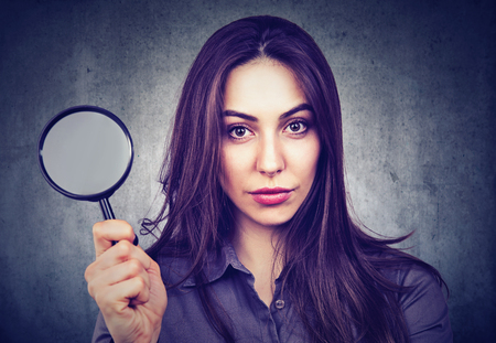 Beautiful woman with magnifying glass isolated on gray wall background.