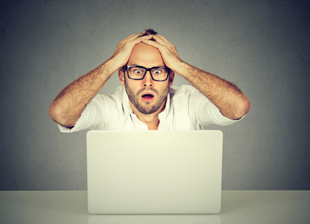 Shocked young man looking at laptop computer anxious with open mouth and big eyes hands on head in disbelief. Human emotion reaction Stock Photo