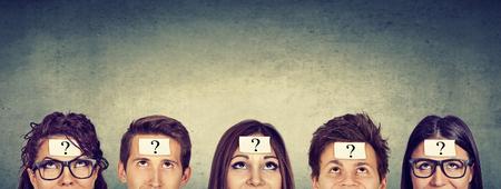 Wieloetniczne grupa myślących ludzi ze znakiem zapytania patrząc w górę Zdjęcie Seryjne