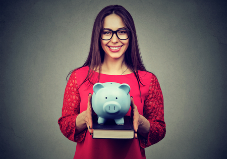 fondo de graduacion: Smiling student, happy woman, holding books and piggy bank in hands. Value of education concept. College fund savings Foto de archivo