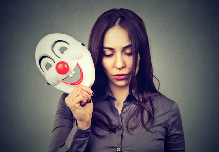 hypocrisy: Sad woman with clown mask Stock Photo