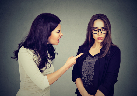 Angry woman scolding her scared shy young sister or friend isolated on gray wall background