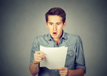 Shocked man holding some documents, isolated on gray background
