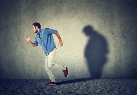 Man running away from his sad gloomy fat shadow on the wall. Mental health and body weight control concept Stockfoto