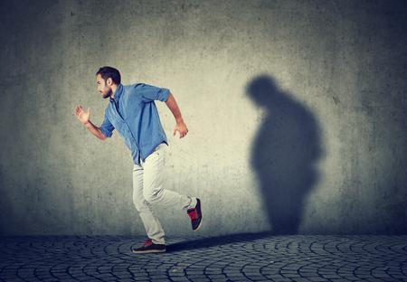 Man läuft weg von seinem traurigen düsteren fetten Schatten an der Wand. Psychische Gesundheit und Körpergewicht Kontrolle Konzept
