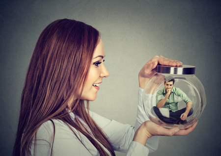 Woman holding a glass jar with imprisoned man in it