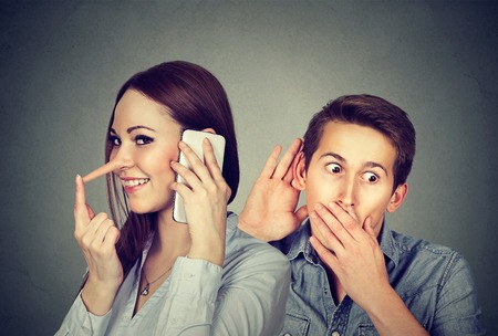 A cheating girlfriend. Curious man secretly listening to a happy woman liar talking on mobile phone with her lover isolated on gray background
