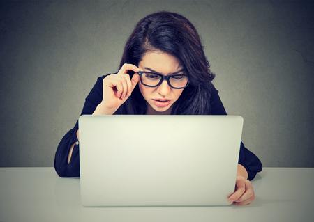 Ongerust gemaakte bedrijfsvrouw die aan laptop werkt die verward het computerscherm kijken