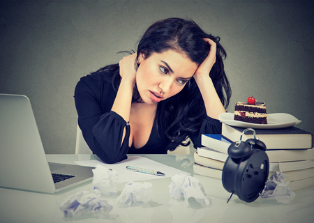 stressed woman sitting at desk in her office overworked craving sweet cake