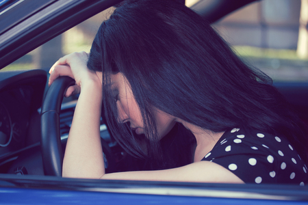 Stressed depressed woman driver sitting inside her car