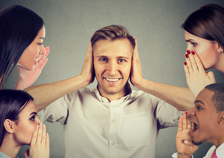 Man and women whispering a secret latest gossip to a happy young man who covers ears and ignoring all surrounding noise