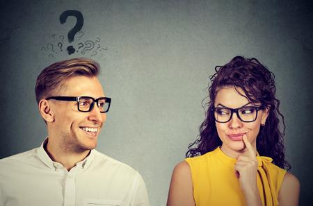 Est-ce qu'elle me plaît? Bel homme avec un point d'interrogation regardant une fille attirante qui flirte avec lui. Les émotions humaines font face à la perception de l'expression Banque d'images - 78947349