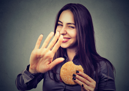 cravings: woman with hamburger rejecting advise on healthy eating