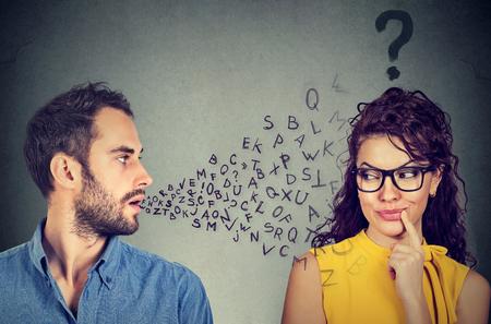 Sprachbarriere Konzept. Stattlicher Mann spricht mit einer attraktiven jungen Frau mit Fragezeichen