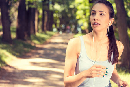 Sporty young woman jogging in the park in sunrise light photo