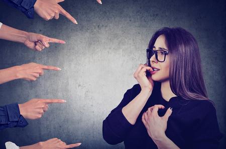Donna ansiosa giudicata da persone diverse. Concetto di accusa di ragazza colpevole. Sensazione negativa di emozioni umane Archivio Fotografico