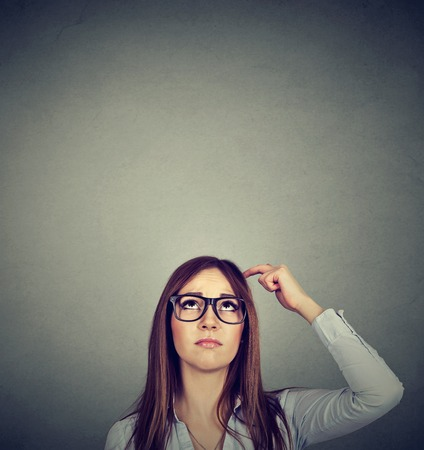 Woman with thoughtful expression looking up on gray wall background