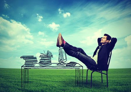 Happy business man relaxing at his desk outdoors in the middle of a green meadow, daydreaming