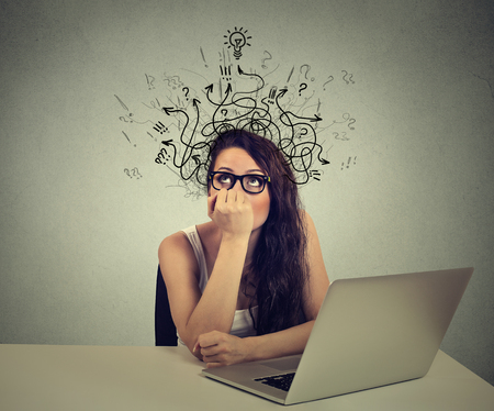 Young woman with thoughtful expression sitting at a desk with laptop with lines arrows and symbols coming out of her head