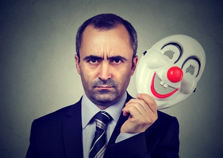 bogus: Angry business man taking off happy clown mask Stock Photo