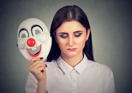 Portrait sad woman taking off clown mask expressing happiness isolated on gray wall background