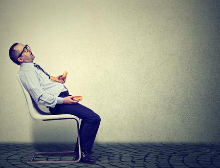 Geschäftsmann fühlt sich müde und schläfrig nach dem Essen zu viele Burger zum Mittagessen Standard-Bild - 81314875