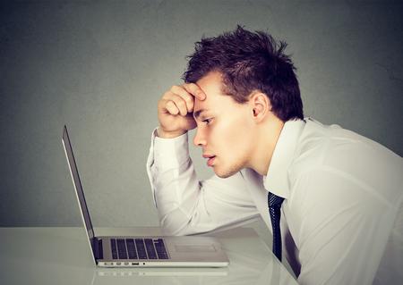 Ongelukkige benadrukte verdrietige man die aan het bureau zit voor zijn laptop