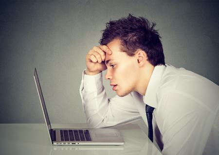 Unhappy stressed sad man sitting at desk in front of his laptop