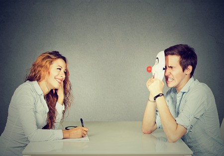 Woman interviewing new candidate for a job, a man pretender hiding his real personality Standard-Bild