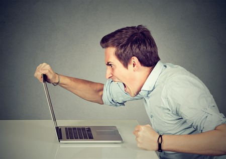 Entrepreneur angry and furious with a laptop in his office or home