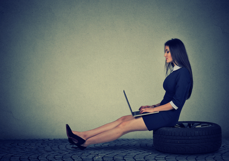 Woman sitting on a car tire working on laptop