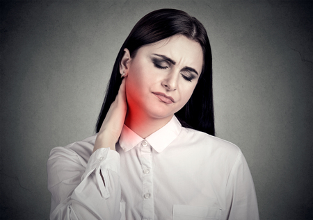 Woman massaging painful neck colored in red isolated on gray wall background. Human face expression.
