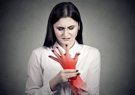 Woman holding her painful wrist isolated on gray wall background. Pain location indicated by red spot. Stock Photo