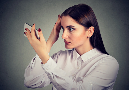 Upset woman surprised she is losing hair has receding hairline. Human emotion. Stock Photo