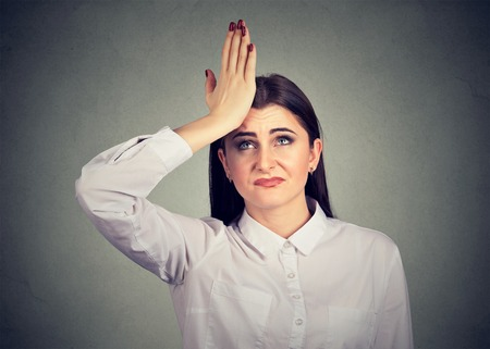 Closeup portrait silly woman, slapping hand on head having duh moment isolated on gray. Negative human emotion feeling, body language, reaction Stock Photo