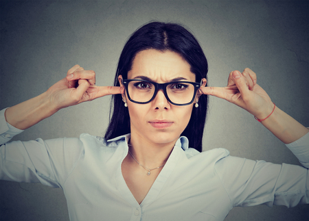 stubbornness: Angry woman plugging her ears with fingers Stock Photo