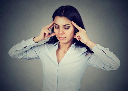 vertigo: sad young woman with worried stressed face expression having headache Stock Photo