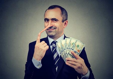 Financieel fraudeconcept. Leugenaarzakenman met dollarcontant geld