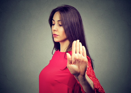 Closeup portrait angry woman giving talk to hand gesture with palm outward isolated gray wall background. Negative human emotion body language