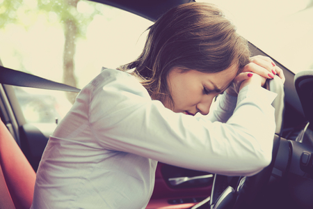 Stressed woman driver sitting inside her car Imagens