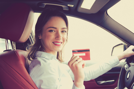 Happy woman sitting inside her new car showing credit card