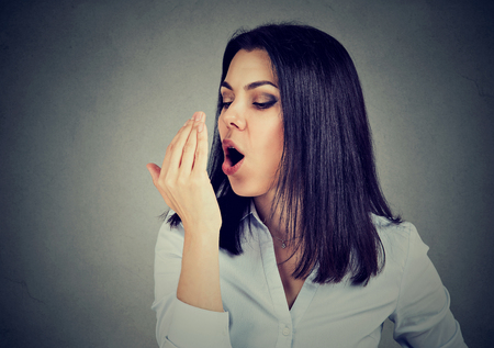 Woman checking her breath with hand.