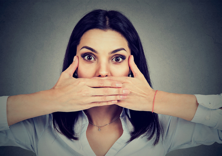 Woman covers her mouth to keep from screaming isolated on gray background Stock Photo